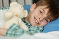 有他的说谎在他的床上的玩具熊的愉快的男孩 免版税库存图片