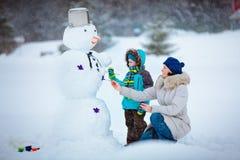 有他的绘雪人的母亲的小男孩 库存照片