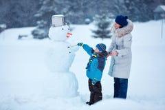 有他的绘雪人的母亲的小男孩 库存图片
