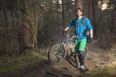 有他的ATB的年轻人在森林里 免版税库存照片