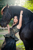 有黑皇家礼服的时兴的夫人在棕色马附近 摆在与马的豪华庄重装束的美丽的少妇 免版税库存图片