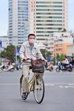 有嘴盖帽的在自行车,昆明,中国人 免版税库存照片