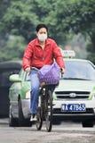 有嘴盖帽的骑自行车者有在背景,广州,中国的出租汽车的 免版税库存图片