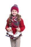 有戴着被编织的毛线衣、围巾、帽子和手套与冰鞋的卷曲发型的逗人喜爱的微笑的小女孩隔绝在白色 库存图片
