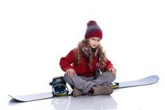 有戴着被编织的毛线衣、围巾、帽子和手套的卷曲发型的微笑的小女孩坐蓝色雪板,被隔绝 免版税图库摄影