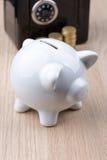 有黑硬币后面的白色存钱罐 免版税图库摄影