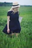 有黑礼服的妇女在绿色麦子的领域 免版税图库摄影