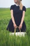 有黑礼服的妇女在绿色麦子的领域 库存图片