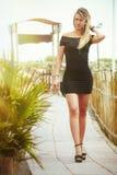 有黑礼服的白肤金发的女孩走沿道路的 库存照片