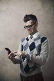有滑稽的人与他的智能手机的困难 图库摄影