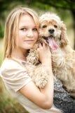 有滑稽的看的狗的逗人喜爱的女孩 库存图片