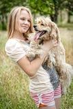有滑稽的看的狗的逗人喜爱的女孩 免版税库存图片
