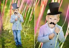 有滑稽的纸髭和帽子的小男孩 户外快乐的儿童的假日 图库摄影