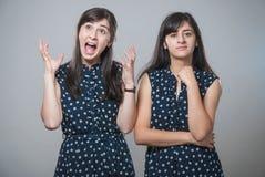 有滑稽的面孔的两个姐妹 免版税库存图片
