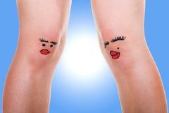 有滑稽的面孔的两条女性腿 库存图片