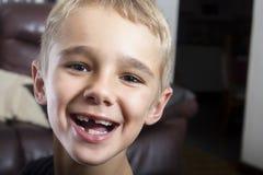 有滑稽的面孔的逗人喜爱和滑稽的年轻男孩 图库摄影
