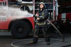 有水水管的消防队员在卡车附近 库存照片