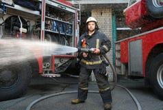 有水水管的消防队员在卡车附近 免版税库存图片