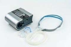 有水管的CPAP鼻子的机器和面具 人的治疗有睡眠停吸的 免版税库存图片