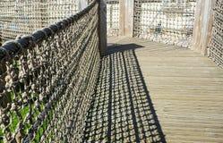 有绳索篱芭的木走的桥梁 免版税库存图片