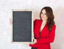 有黑粉笔板的少妇 免版税库存照片