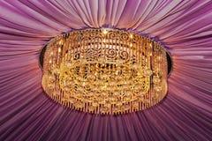 有紫罗兰色帷幕的金黄枝形吊灯 库存图片