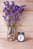 有紫罗兰色花的时钟在木背景 图库摄影