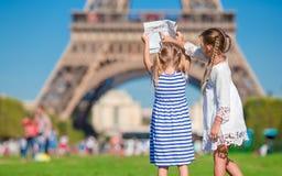 有巴黎背景地图的可爱的小女孩  库存图片