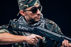 有黑背景概念的全副武装的被掩没的战士 库存图片