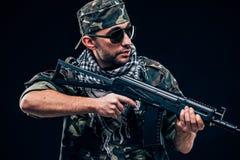 有黑背景概念的全副武装的被掩没的战士 库存照片