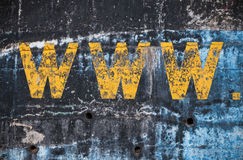 有黄色万维网标签的深蓝混凝土墙 库存图片