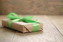 有绿色丝带弓的土气工艺纸礼物盒在木桌上 库存照片