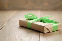 有绿色丝带弓的土气工艺纸礼物盒在木桌上 库存图片