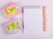 有绿色丝带的两个一点礼物盒和有一张空白页的开放笔记本 免版税库存图片