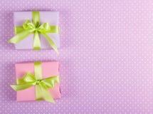 有绿色丝带的两个一点礼物盒在与圆点的柔和的背景 库存照片