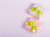 有绿色丝带的两个礼物盒在与圆点的柔和的背景 免版税库存图片
