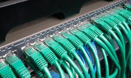 有绿色互联网插接线的服务器机架缚住 免版税库存照片