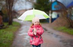 有绿色伞的小微笑的愉快的女孩在春天 免版税库存图片