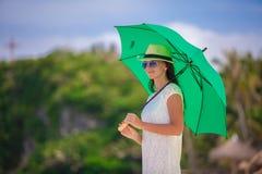 有绿色伞走的时尚少妇 免版税库存照片