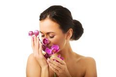 有紫色兰花分支的露胸部的妇女 免版税图库摄影
