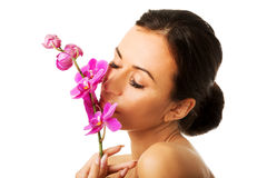 有紫色兰花分支的露胸部的妇女 免版税库存照片