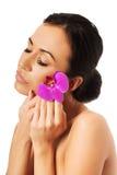 有紫色兰花和闭合的眼睛的妇女 免版税库存照片