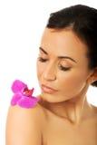 有紫色兰花瓣的妇女在肩膀 库存照片