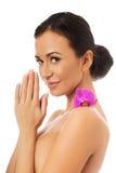 有紫色兰花瓣的妇女在肩膀 免版税库存照片