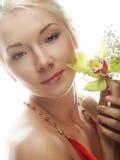 有绿色兰花花的美丽的白肤金发的妇女 免版税图库摄影