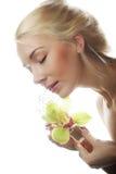 有绿色兰花花的美丽的白肤金发的妇女 库存图片
