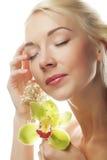 有绿色兰花花的美丽的白肤金发的妇女 免版税库存照片