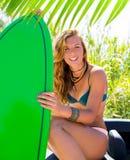 有绿色冲浪板的白肤金发的青少年的冲浪者女孩在汽车 免版税库存图片