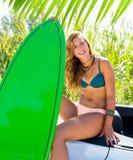 有绿色冲浪板的白肤金发的青少年的冲浪者女孩在汽车 免版税库存照片