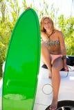 有绿色冲浪板的白肤金发的青少年的冲浪者女孩在汽车 免版税图库摄影
